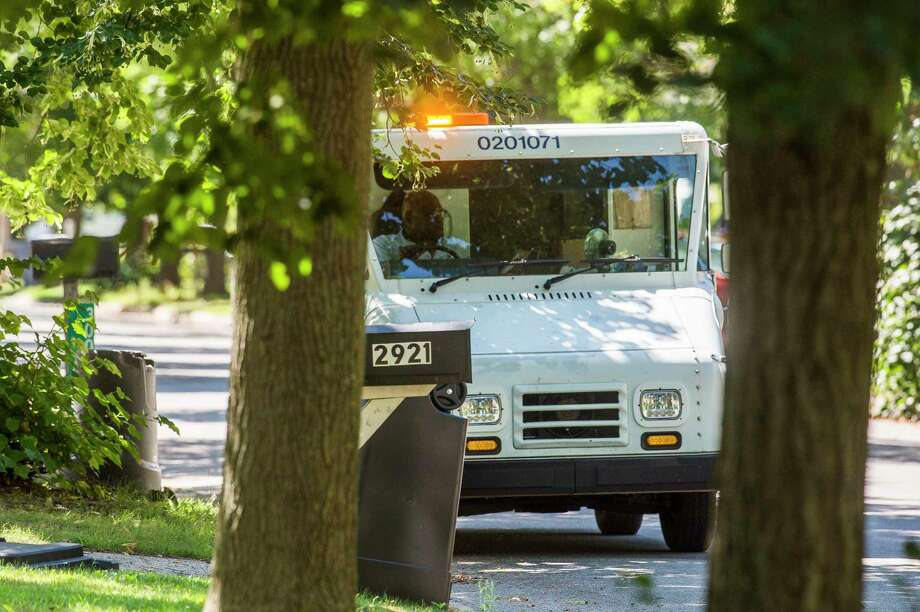Charles Thomas, a mail carrier with the USPS, delivers mail Monday afternoon on Riggie Street in Midland. (Katy Kildee/kkildee@mdn.net)
