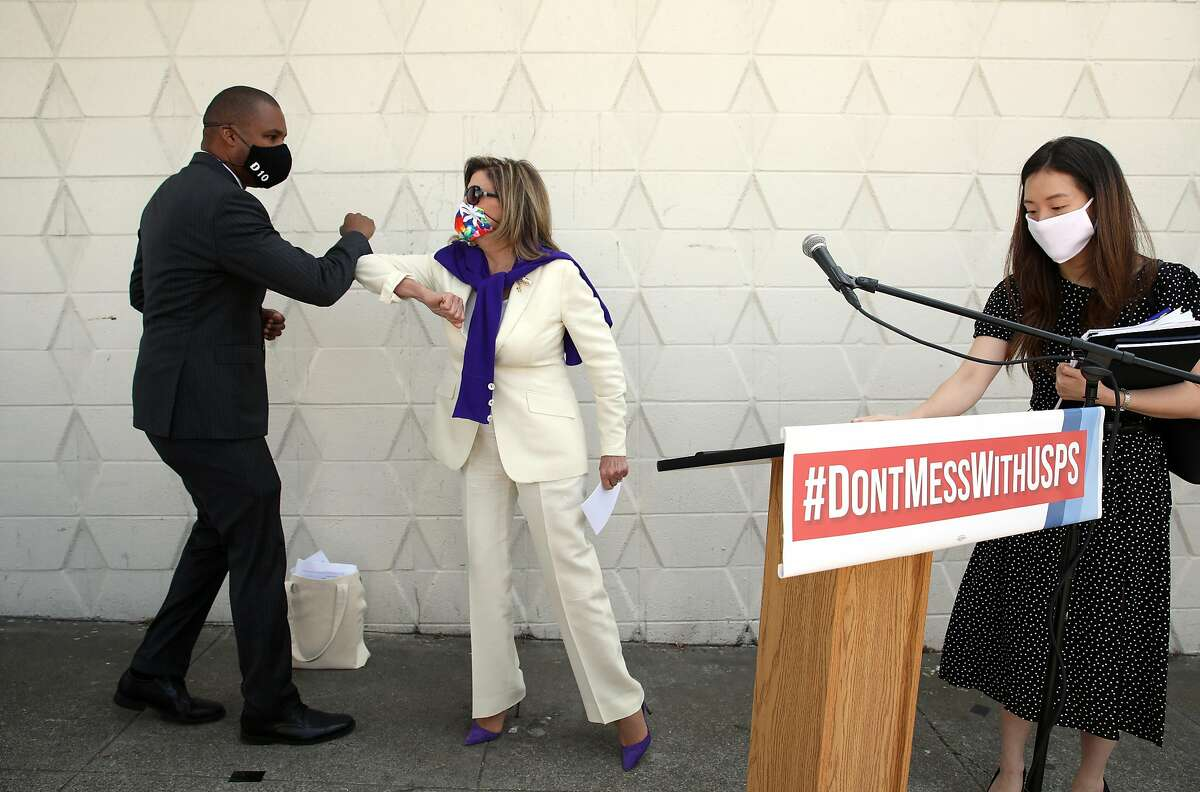 Nancy Pelosi (middle) is greeted by district supervisor Shamann Walton (left) as they get ready to talk against what the Trump administration is doing to the USPS at the Bayview post office on Tuesday, Aug. 18, 2020, in San Francisco, Calif.