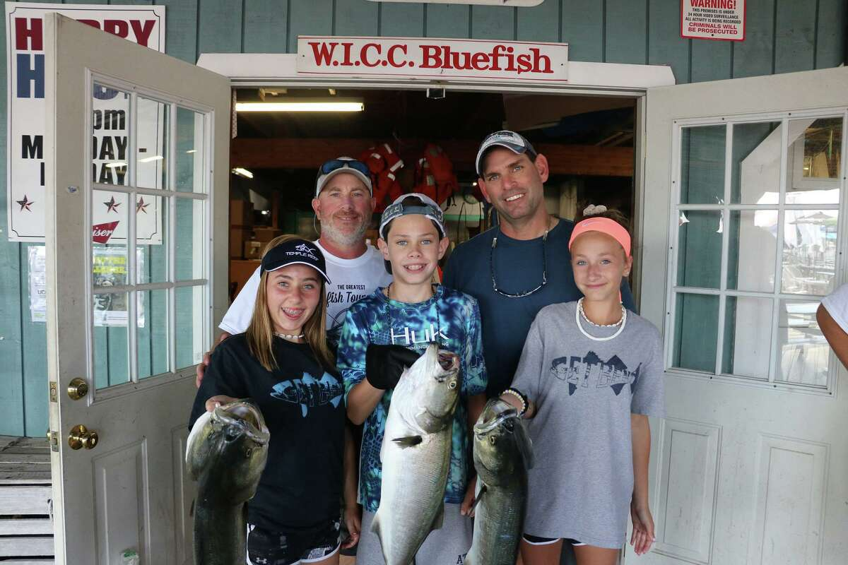 """""""The WICC 600 Spector Eye Care Greatest Bluefish Tournament on Earth"""" takes place Aug. 29 and 30 on Long Island Sound. Family members are seen here at Captain's Cove in Bridgeport, where they gathered last year to display fish caught during the 2019 event. The tournament, which attracts thousands of participants, is in its 38th year."""