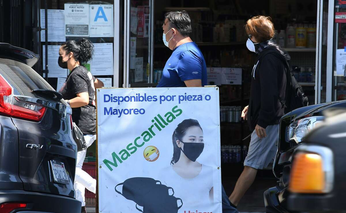 People walk past a store selling face coverings in the largely Latino neighbor of East Los Angeles, August 7, 2020 in Los Angeles, California during the coronavirus pandemic. - California is experiencing a statewide spike in COVID-19 infections among Latinos, both in urban areas as well as rural, farm-working communities according to reports in the Los Angeles Times. (Photo by Robyn Beck / AFP) (Photo by ROBYN BECK/AFP via Getty Images)