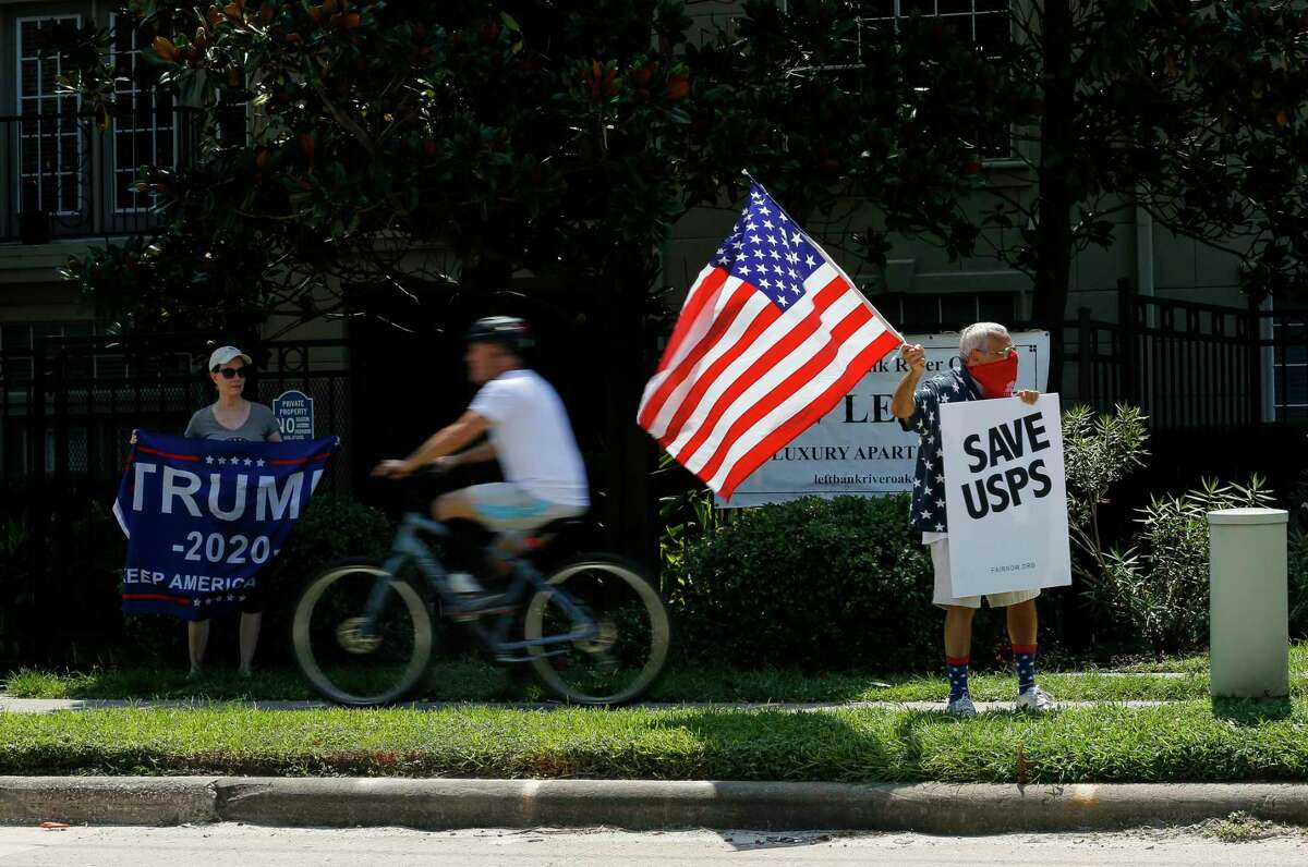 """Rachal Smith, left, shows her support for President Donald Trump, as Ira Dember, right, waves an American flag and holds up a sign that reads """"Save USPS,"""" during a protest outside Senator John Cornyn's office Tuesday, Aug. 18, 2020, in Houston."""