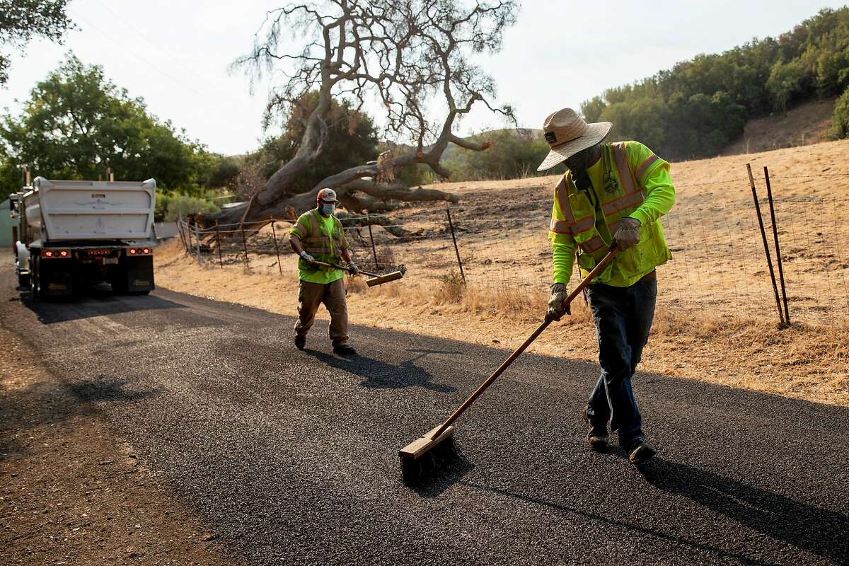 Contra Costa Public Works maintenance crews work to even out a chip seal operation on Christie Road in Martinez, Calif. Tuesday, August 18, 2020. City employees and road crews have been working in extreme temperatures during the Bay Area heat wave and stay cool by wearing shaded hats and drinking water consistently.