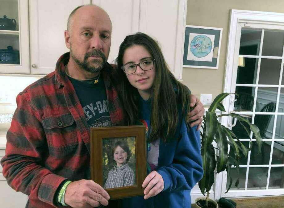 In this Dec. 3, 2019, photo, Mark Barden and his daughter Natalie Barden hold a photograph of Natalie's late brother, Daniel, at their home in Newtown, Conn. Daniel died in the Dec. 14, 2012, Sandy Hook School shooting that killed 20 first graders and six educators. Natalie, 17, is among Newtown students who have grown up to become young voices in the gun violence prevention movement. Photo: Dave Collins / Associated Press