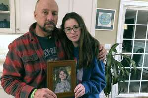 In this Dec. 3, 2019, photo, Mark Barden and his daughter Natalie Barden hold a photograph of Natalie's late brother, Daniel, at their home in Newtown, Conn. Daniel died in the Dec. 14, 2012, Sandy Hook School shooting that killed 20 first graders and six educators. Natalie, 17, is among Newtown students who have grown up to become young voices in the gun violence prevention movement.