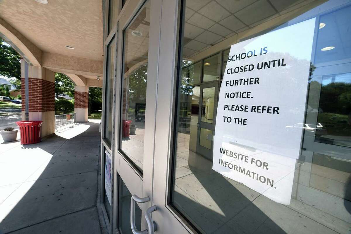 A sign on the school's closure in the spring remained on an entrance door to Wilbur Cross High School in New Haven on Aug. 18, 2020. School opeded remotely on Sept. 3.