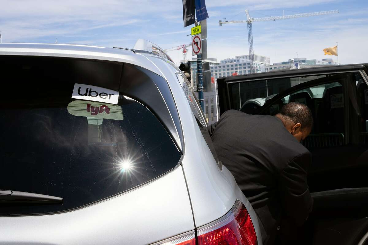 FILE -- A passenger exits a rideshare car in San Francisco on June 28, 2019. Uber and Lyft have separately discussed plans to license their technology to those who want to operate fleets of ride-hailing cars in California. (Sarahbeth Maney/The New York Times)