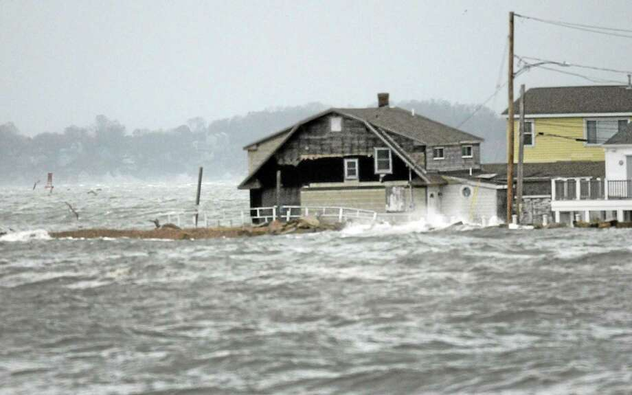 A house goes under water as Hurricane Sandy picks up speed with waves from Long Island Sound and hits the Cosey Beach area of East Haven Oct. 29, 2012. Natural disasters such as these are projected to increase in the coming years due to climate change, Middletown environmentalists say. Photo: Hearst Connecticut Media File Photo / ©Peter Hvizdak /  New Haven Register