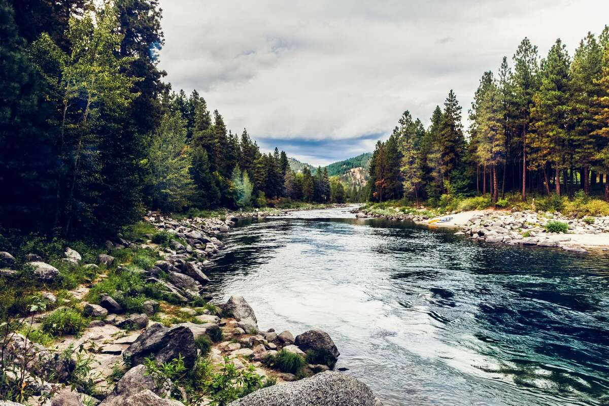 A scenic and tree lined landscape of Wenatchee River taken near Leavensworth, Washington state, USA on an overcast day. High resolution color photograph with horizontal composition and room for your copy.