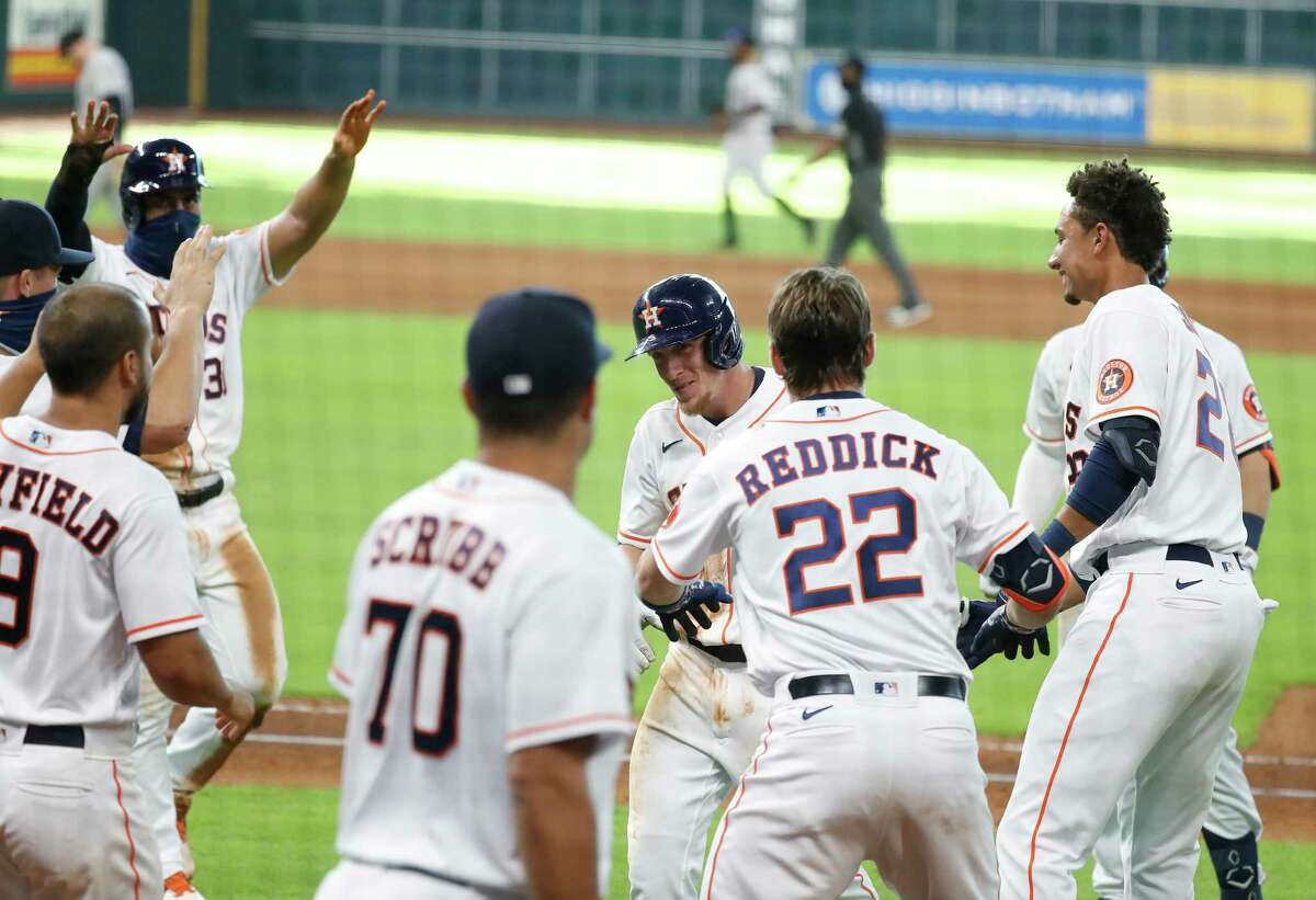 Houston Astros Myles Straw (3) is surrounded by teammates as they celebrated after Straw hit an RBI single which allowed Abraham Toro to score the winning run during the eleventh inning of an MLB baseball game at Minute Maid Park, Tuesday, August 18, 2020, in Houston. Astros beat the Colorado Rockies 2-1.