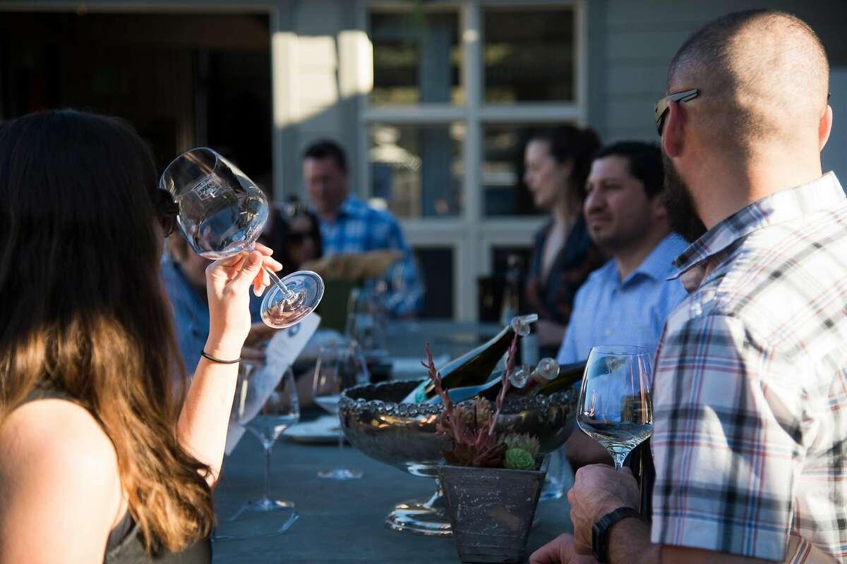 Customers taste wines at Joyce Vineyards' newly built outside bar at their tasting room in Carmel Valley, Calif. in February 2018.