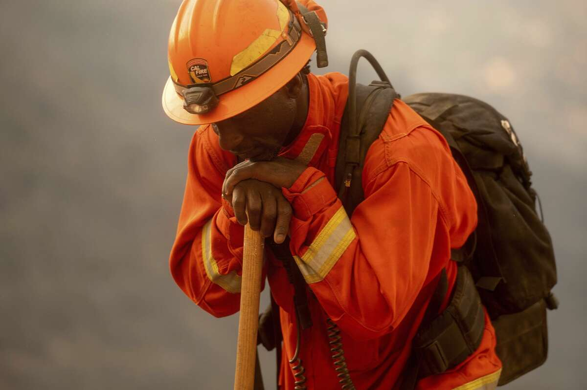 An inmate firefighter rests during a break from battling the River Fire in Salinas. Fire crews across the region scrambled to contain dozens of blazes sparked by lightning strikes as a statewide heat wave continues.