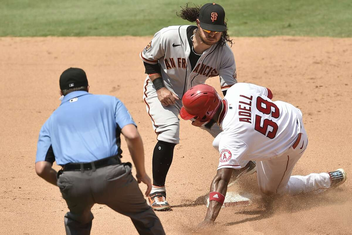 San Francisco Giants shortstop Brandon Crawford, left, tags out Los Angeles Angels' Jo Adell on a steal attempt during the fourth inning of a baseball game in Anaheim, Calif., Tuesday, Aug. 18, 2020. (AP Photo/Kelvin Kuo)