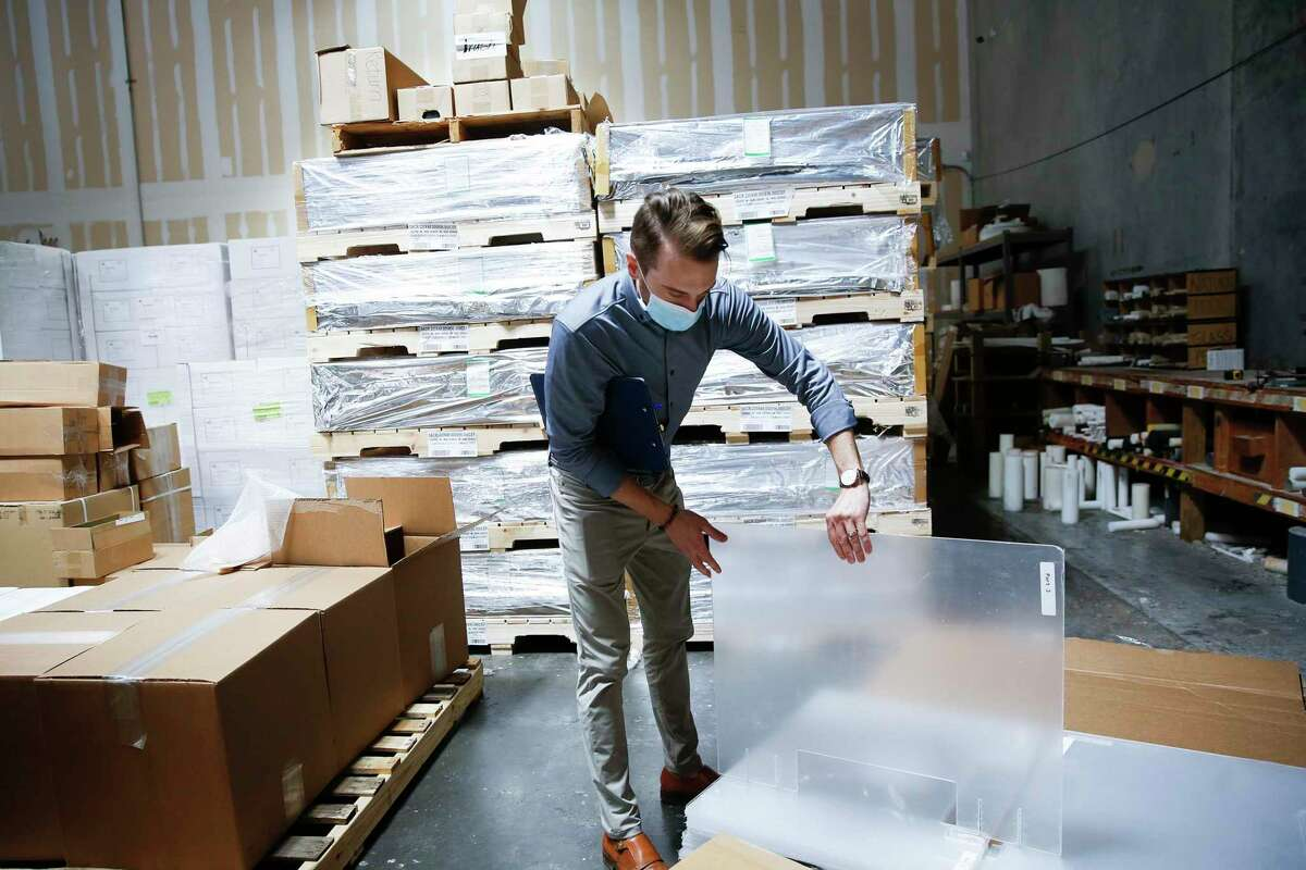 Professional Plastics' Houston business manager Michael Meade demonstrates one of the company's dividers in the warehouse in Stafford on Thursday, Aug. 13, 2020. The company had $10,000 worth of raw acrylic on hand to meet demand early in the pandemic, but now it has more than $1 million's worth.