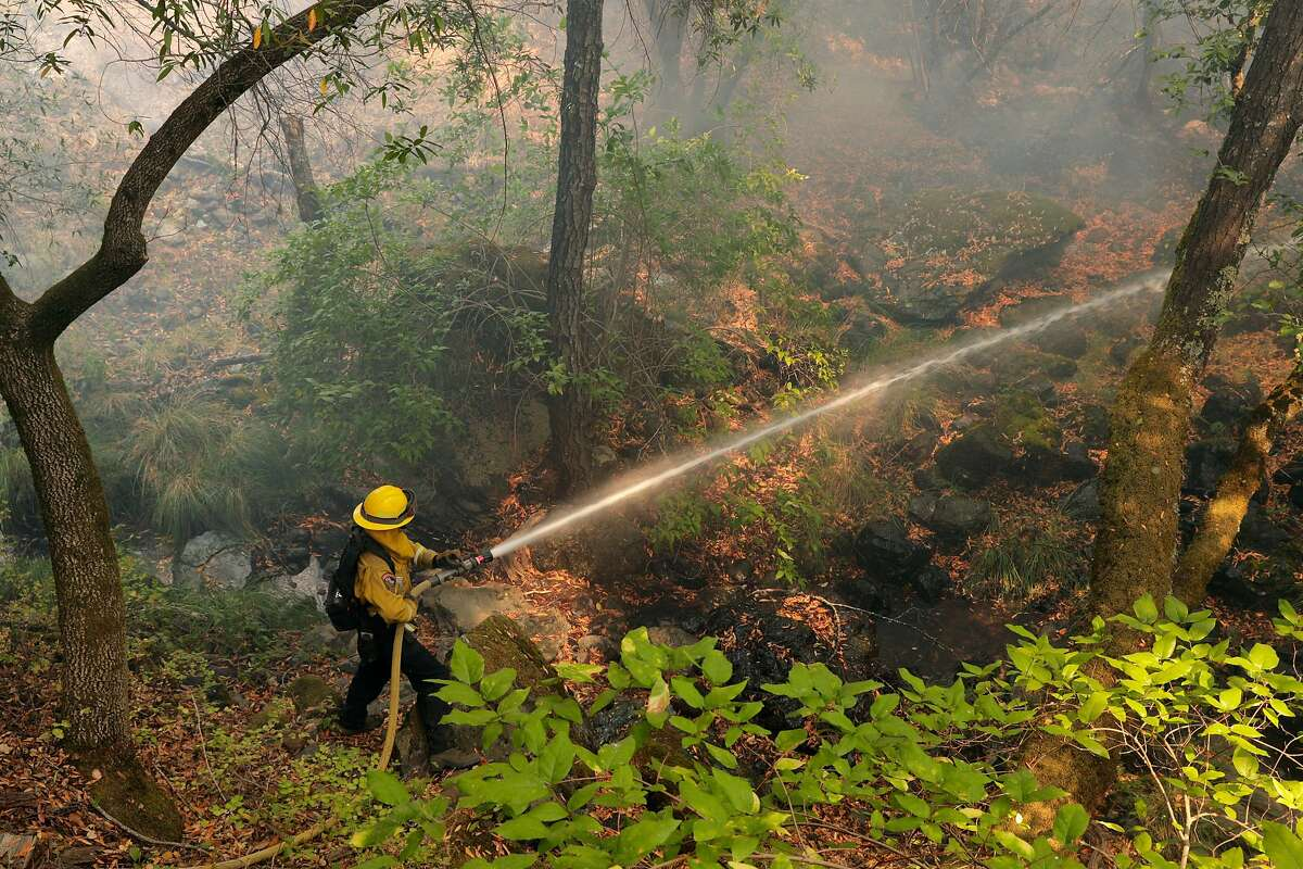 A firefighter with CalFire puts out a spot fire at the 130-year-old Nichelini Winery which was threatened by the Hennessey Fire near St. Helena, Calif., on Tuesday, August 18, 2020.