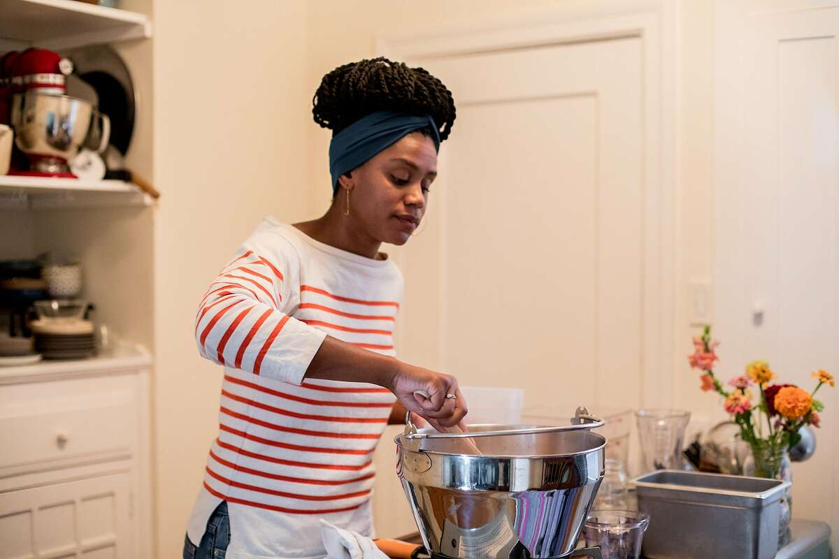 Shakirah Simley, master food preserver and director of the Office of Racial Equity for the city and county of San Francisco, makes peach preserves in her apartment in San Francisco on August 8, 2020. Simley turns off the heat before adding sugar to her peach preserves.