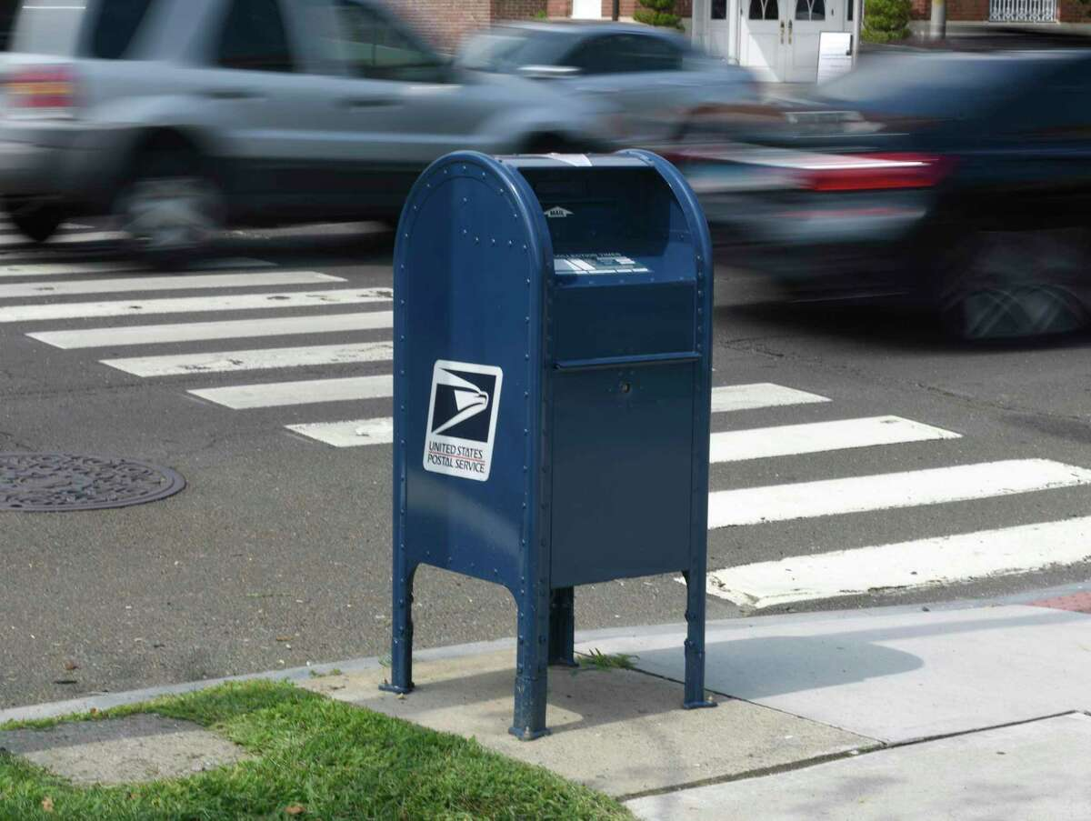 A Cars pass by a USPS mailbox along the Post Road in central Greenwich, Conn. Monday, Aug. 17, 2020.