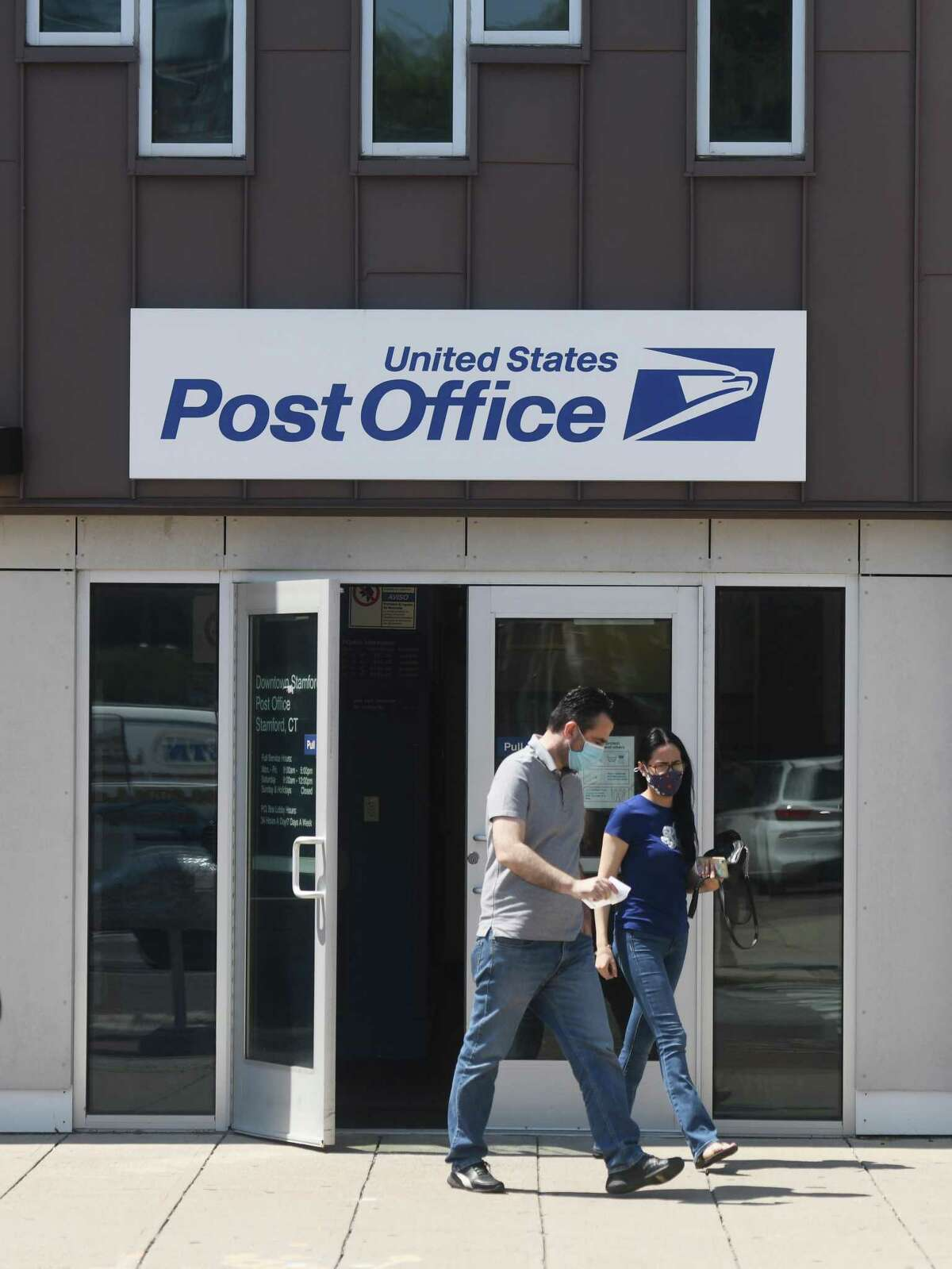 Customers exit the U.S. Post Office on Summer Street in Stamford on Monday.