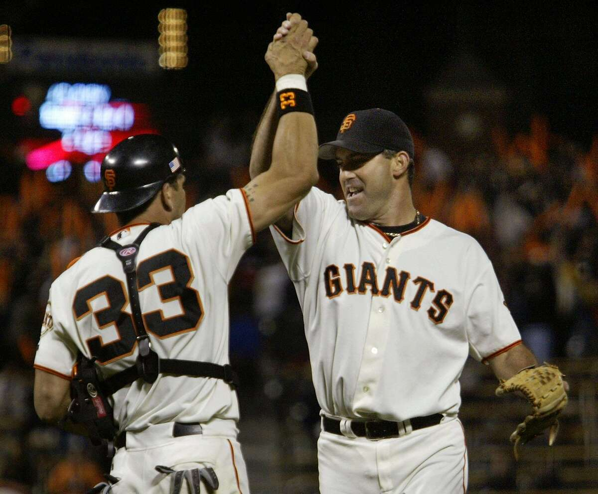 San Francisco Giants Benito Santiago (L) slaps hands with pitcher Robb Nen after they defeated the St. Louis Cardinals in Game 4 of the National League Championship Series in San Francisco October 13, 2002. San Francisco defeated St. Louis 4-3 to take a three games to one lead in the series. REUTERS/Dave Kennedy