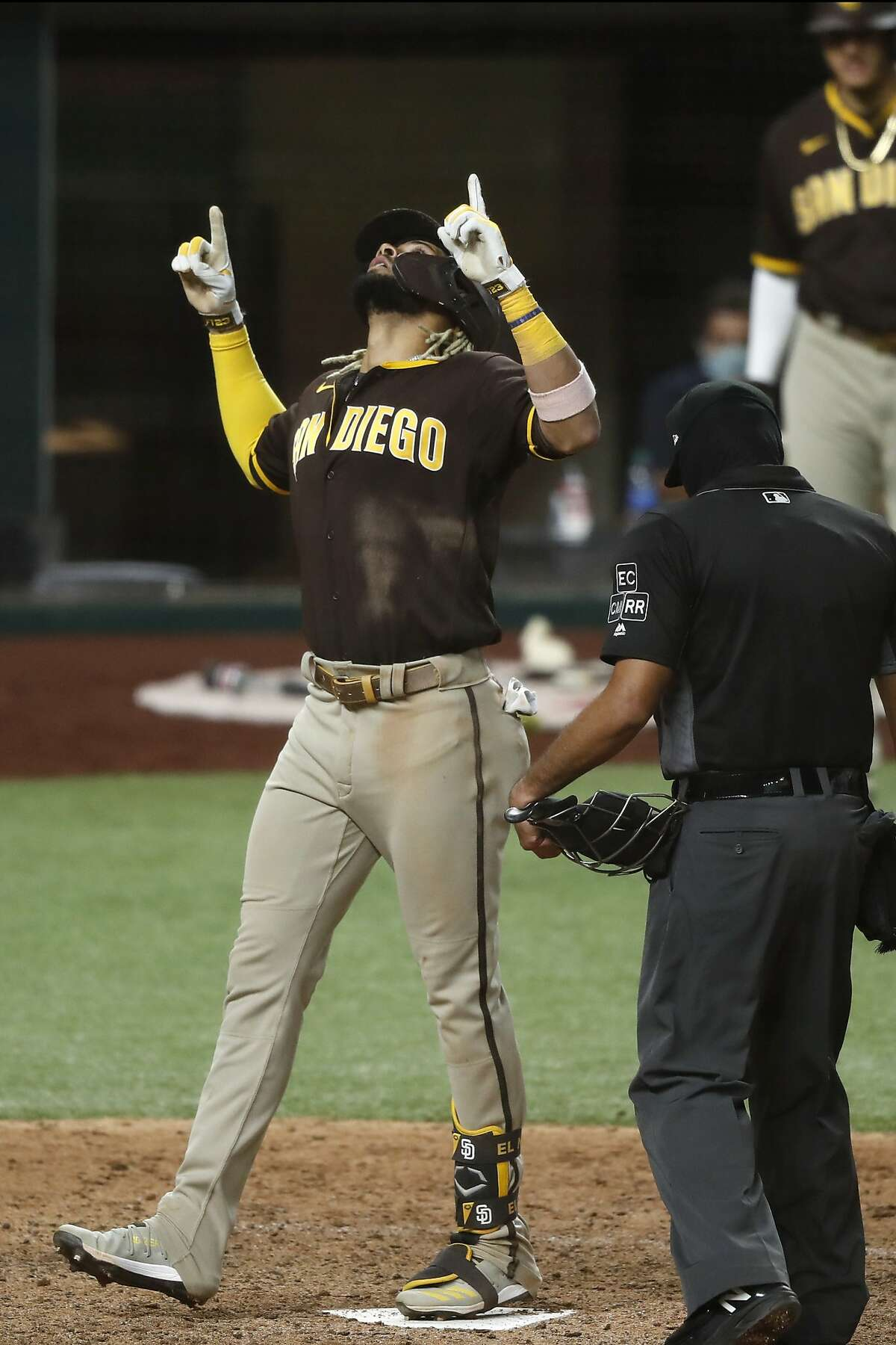 San Diego Padres' Fernando Tatis Jr. celebrates his three-run home run as umpire Nestor Ceja, front, watches him cross the plate in the seventh inning of a baseball game against the Texas Rangers in Arlington, Texas, Monday Aug. 17, 2020. (AP Photo/Tony Gutierrez)