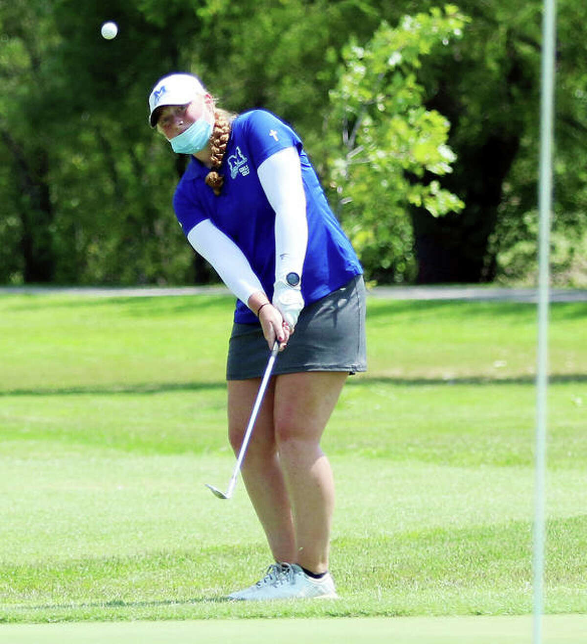 Marquette Catholic junior Gracie Piar chips onto the green at hole No. 7 on Tuesday at the Madison County girls golf tournament at The Legacy in Granite City. Piar shot 1-over par 72 to win overall medalist honors for the first time.