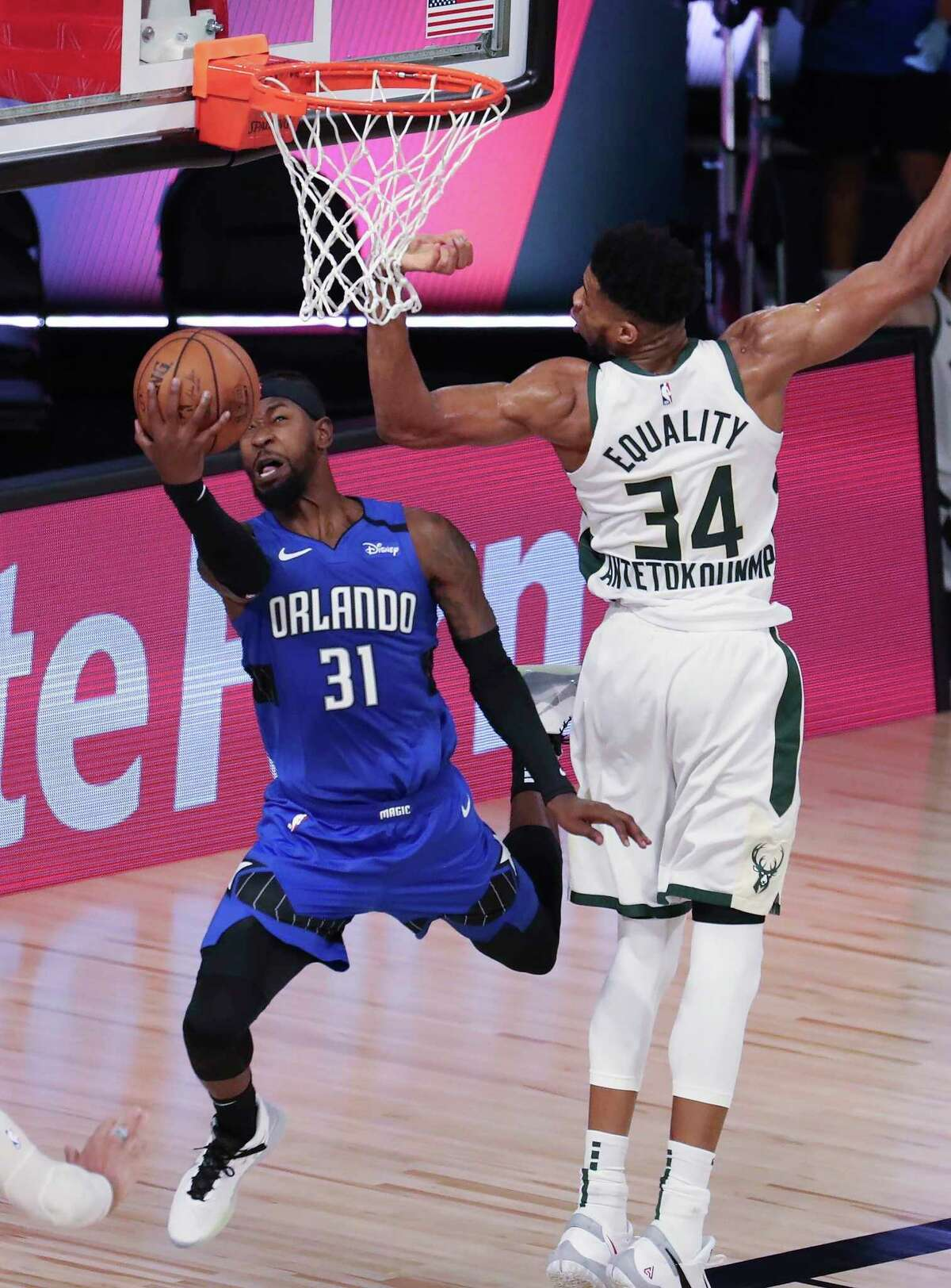 Orlando guard Terrence Ross (31) attempts a reverse lay-up against Milwaukee forward Giannis Antetokounmpo (34) during in Game 1 of an NBA basketball first-round playoff series, Tuesday, Aug. 18, 2020, in Lake Buena Vista, Fla. (Charles King/Orlando Sentinel via AP)