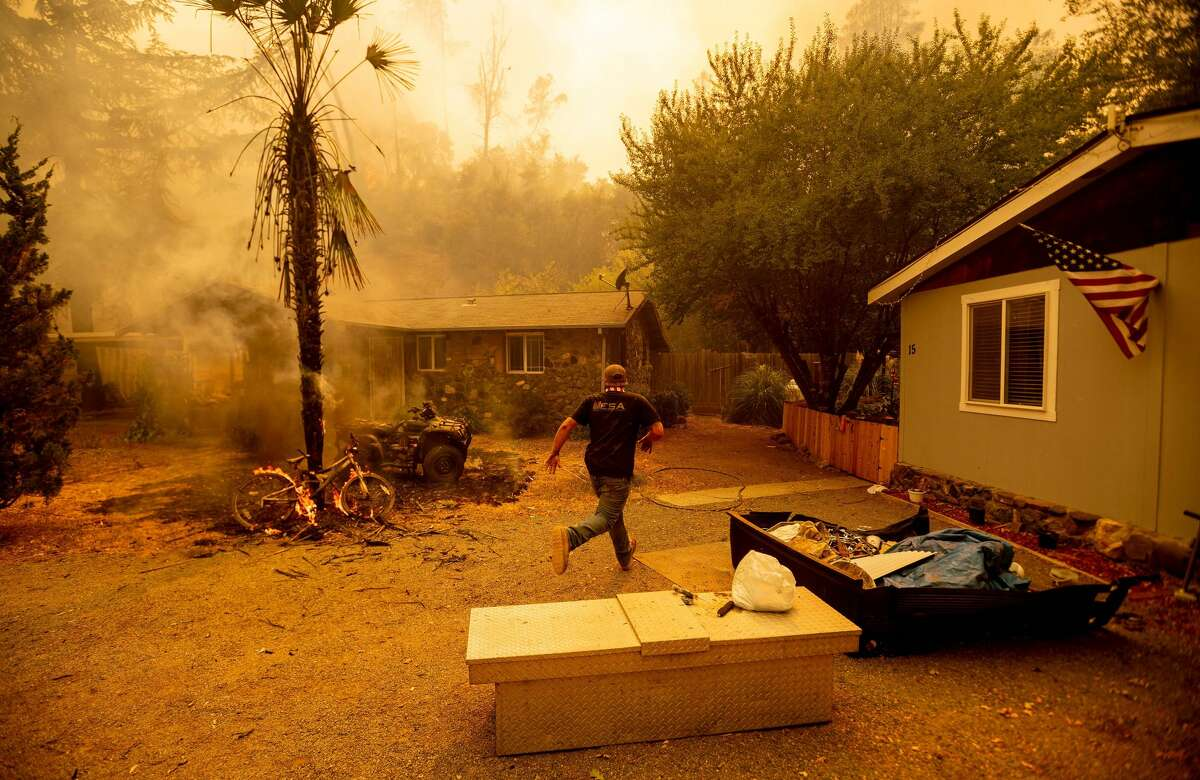 A resident runs into a home to save a dog while flames are getting close as the Hennessey fire continues to rage out of control near Lake Berryessa in Napa, California on August 18, 2020. - The Hennessey Fire started in the early hours of August 17 in the Napa wine region of Northern California. The fire grew to 2,700 acres in 24 hours and is 0% contained. (Photo by JOSH EDELSON / AFP) (Photo by JOSH EDELSON/AFP via Getty Images)