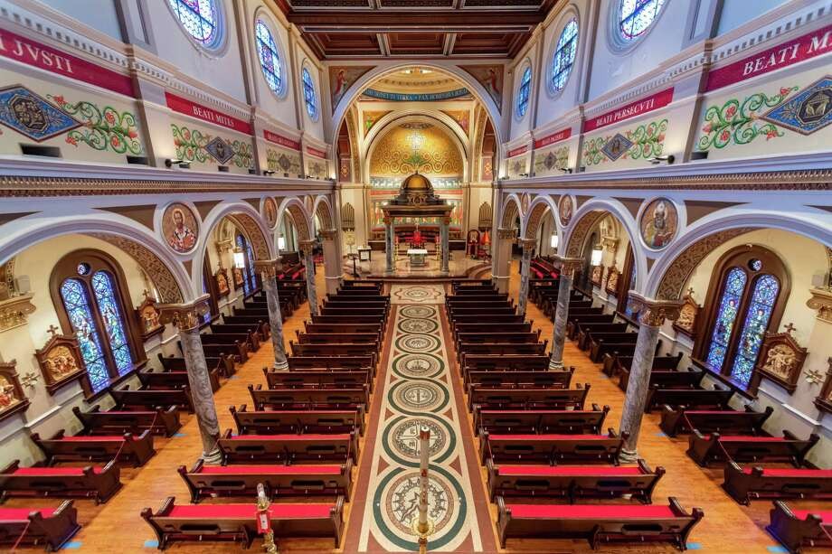 An overhead view of the main sanctuary of St. Anthony Cathedral Basilica from the front vestibule to the altar. The stained glass windows in this part of the church were made in Germany and depict the life of Christ. The Stations of the Cross on the sidewalls are made of porcelain. The Beatitudes are inscribed in the red band toward the time of the photo. The floor of the main aisle leading to the altar is composed of eight mosaics, starting from the back of the church, they depict Humility, Prudence, Justice, Temperance, Fortitude, Reverence, Fear of The Lord, and Charity at the foot of the altar. All of the mosaics are based on or copies of historic works of art in major religious buildings from around the world. Photo made on August 6, 2020. 