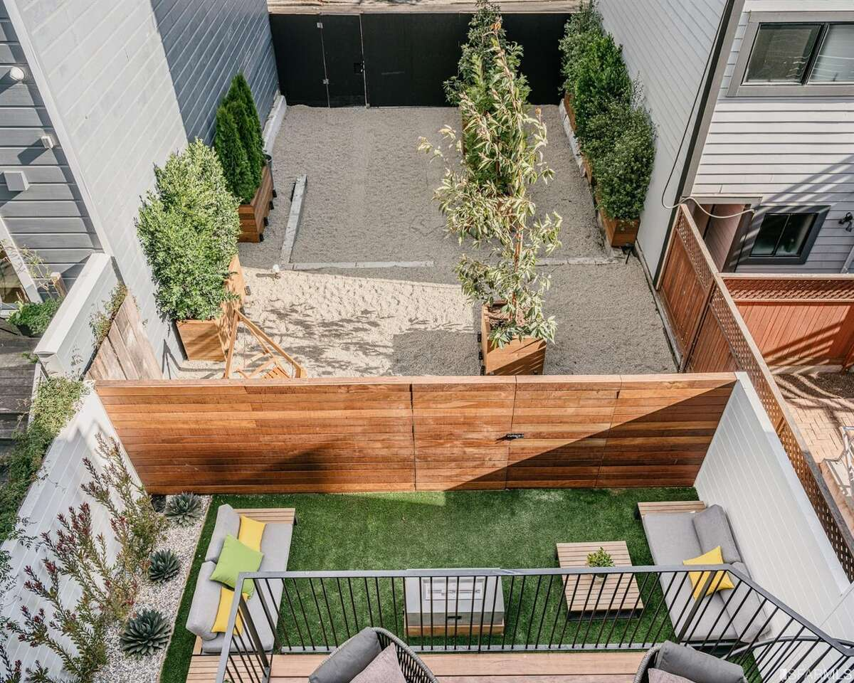 The fence, as seen from the top-floor deck, provides the dividing line between the property that was already included with the home and the additional lot. It is possible to purchase the home and not the extra lot, and the seller has plans for a two-unit building on the space, but Zaludova believes the eventual buyer will prefer to
