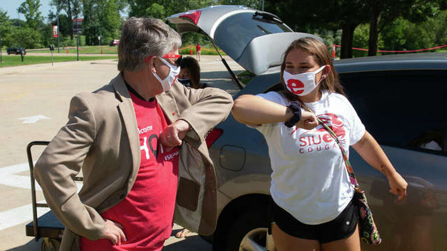 SIUE Chancellor Randy Pembrook, left, greets an SIUE student with an elbow bump during the first of five Move-In Days. Some 2,00 0 students are expected to move in through Saturday at SIUE, with classes starting Monday.