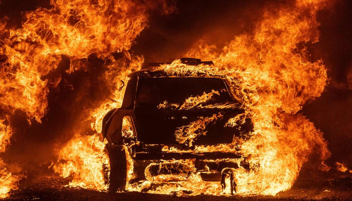 A car burns while parked at a residence in Vacaville, California during the LNU Lightning Complex fire on August 19, 2020. - As of the late hours of August 18,2020 the Hennessey fire has merged with at least 7 fires and is now called the LNU Lightning Complex fires. Dozens of fires are burning out of control throughout Northern California as fire resources are spread thin.