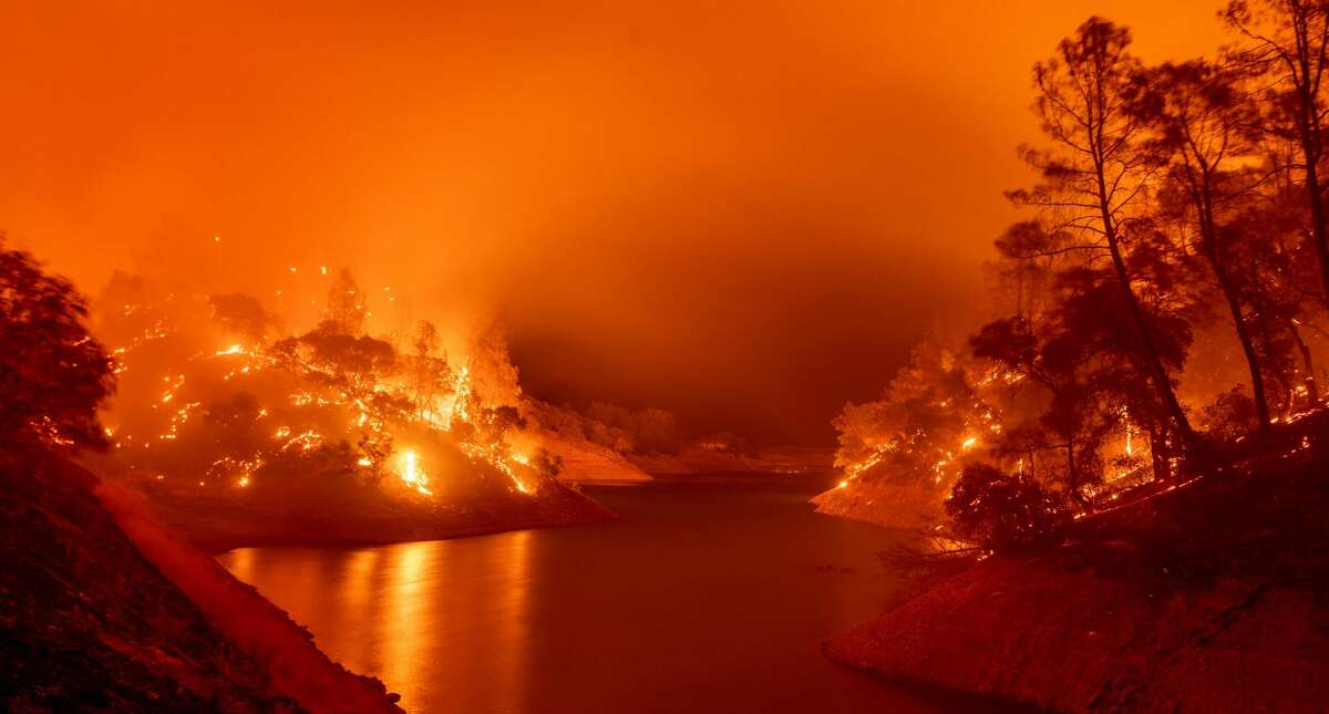 In this long exposure photograph, flames consumes both sides of a segment of Lake Berryessa during the Hennessey fire in the Spanish Flat area of Napa, California on August 18, 2020.