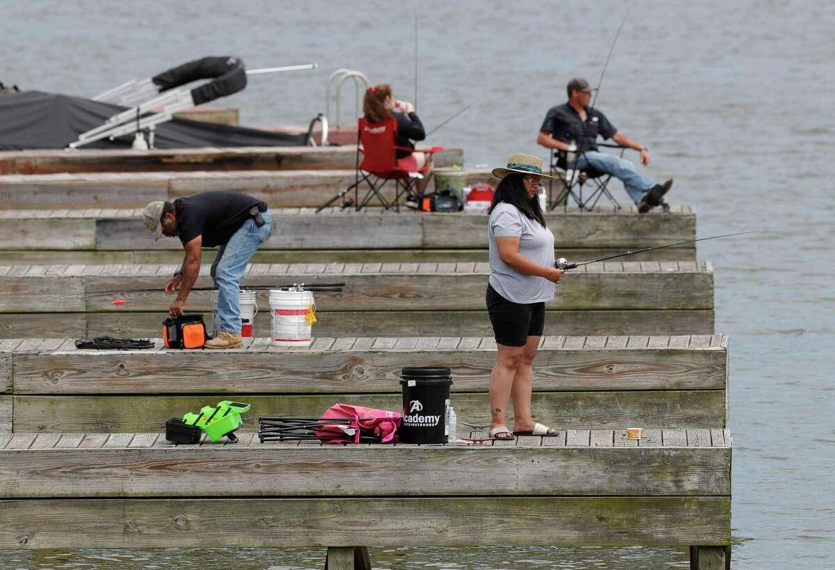People fish off boat docks on Lake Conroe, Saturday, April 25, 2020, in Conroe.