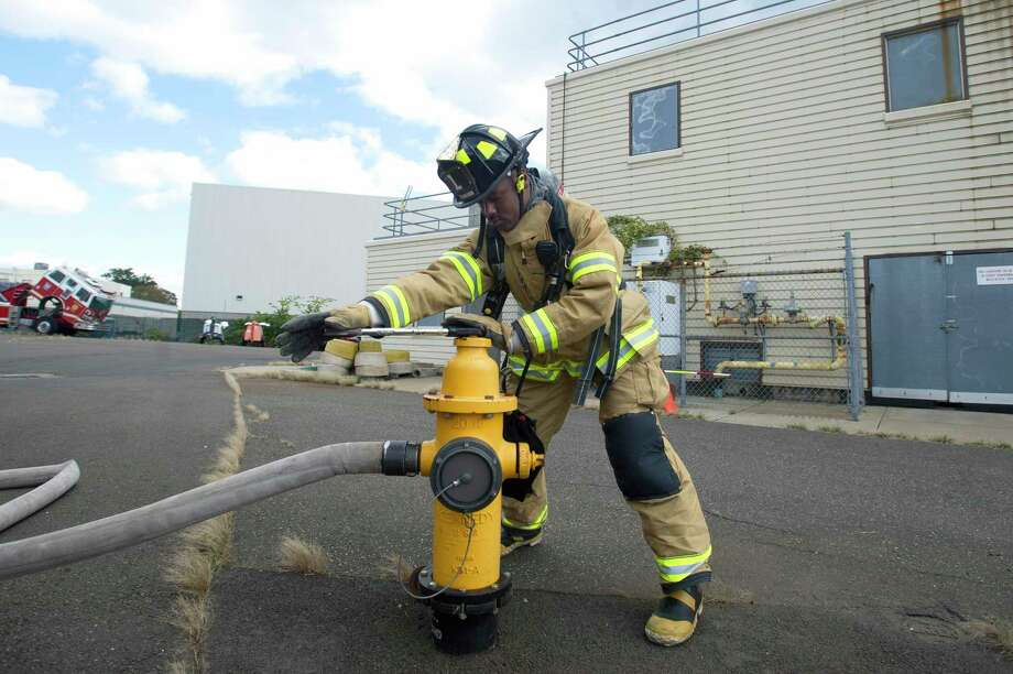 A Stamford firefighter opens a fire hydrant while undergoing training in this 2018 shot. Photo: Hearst Connecticut Media File Photo / Stamford Advocate