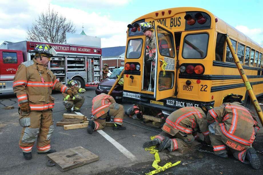 South District Firefighters stabilize a school bus before lifting it to simulate removing a car from under the bus during a heavy vehicle and equipment rescue class in this archive shot. Photo: Hearst Connecticut Media File Photo / TheMiddletownPress