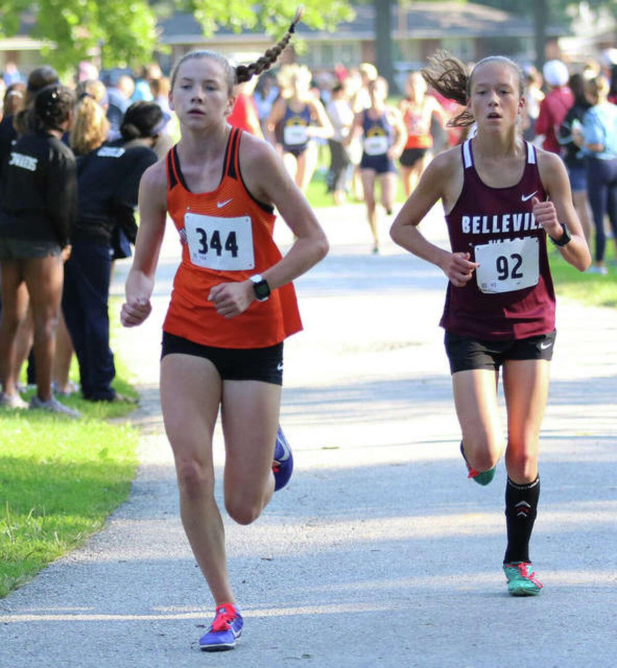 Edwardsville freshman Riley Knoyle (right), shown leading Belleville West's Alyssa Elliott midway through the Granite City Invite on Sept. 7.