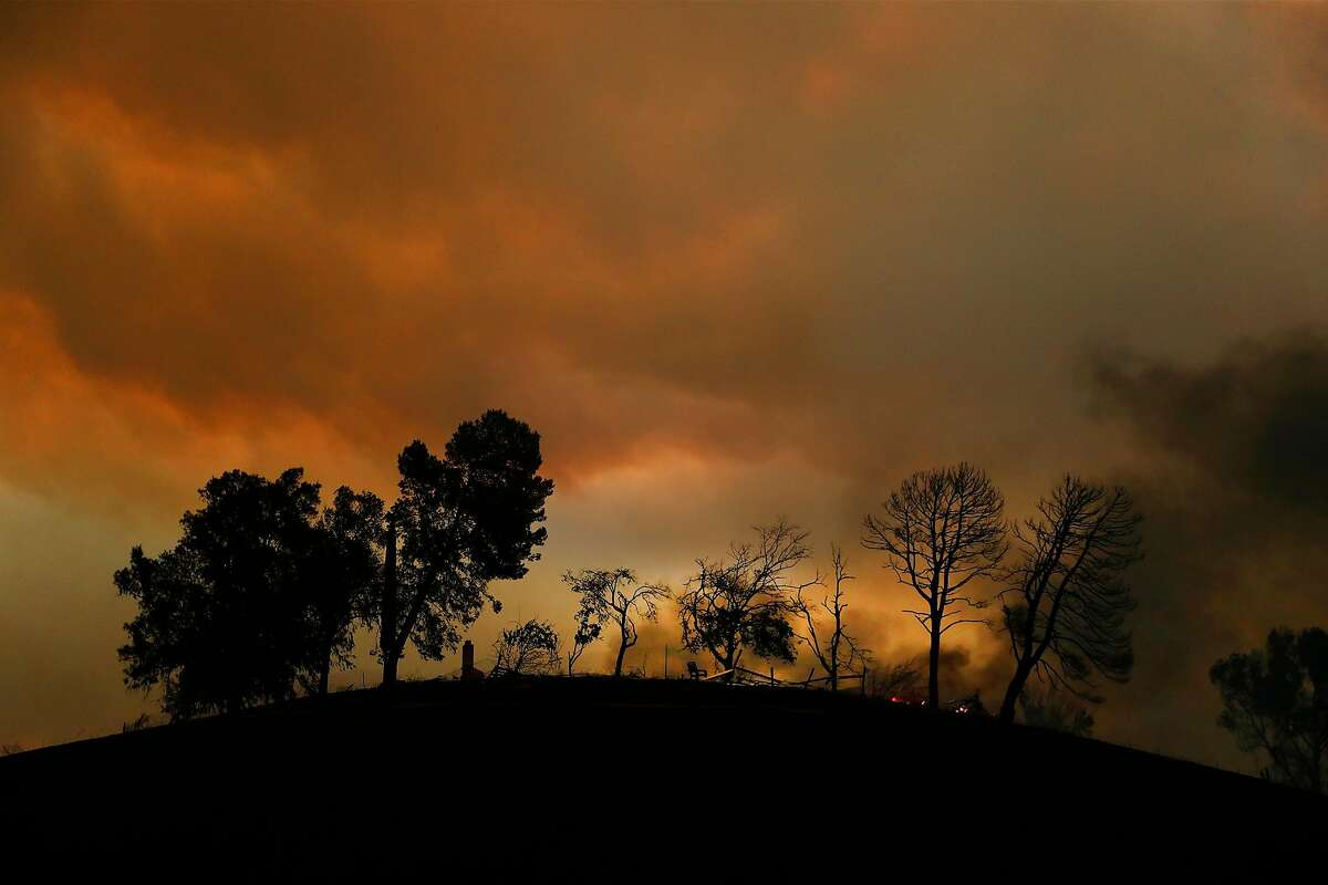 A chimney, a chair and charred trees are all that remain of a homesite on English Hills Road during LNU Lightning Complex Fire in Vacaville , Calif., on Wednesday, August 19, 2020.