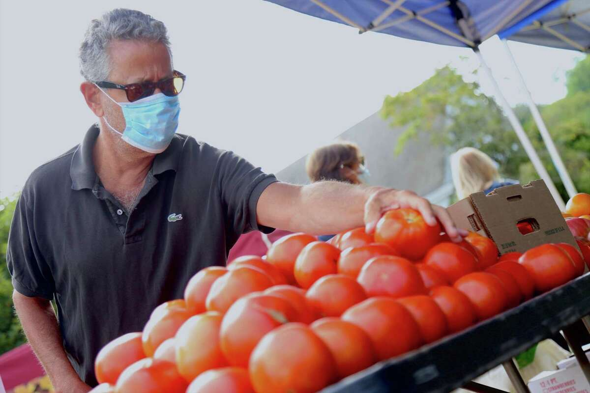Neal Radding of Fairfield makes a tomato choice at the Greenfield Hill Farmer's Market on Saturday, Aug. 15, 2020, in Fairfield, Conn.