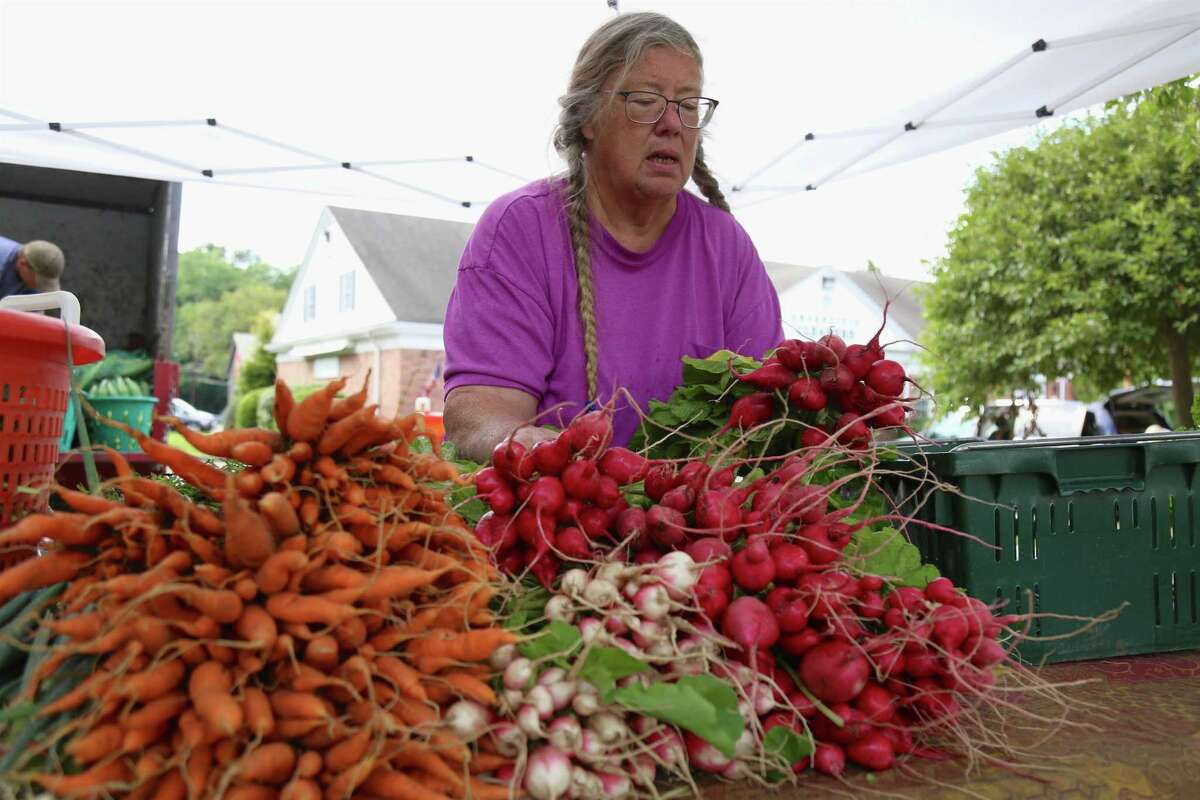 Punky Wilson of Gazy's Farm in Oxford puts out produce at the Greenfield Hill Farmer's Market on Saturday, Aug. 15, 2020, in Fairfield, Conn. Punky Wilson from Oxford-based Gazy's Farm was one of the many vendors with wares to sell and said the market was very popular.