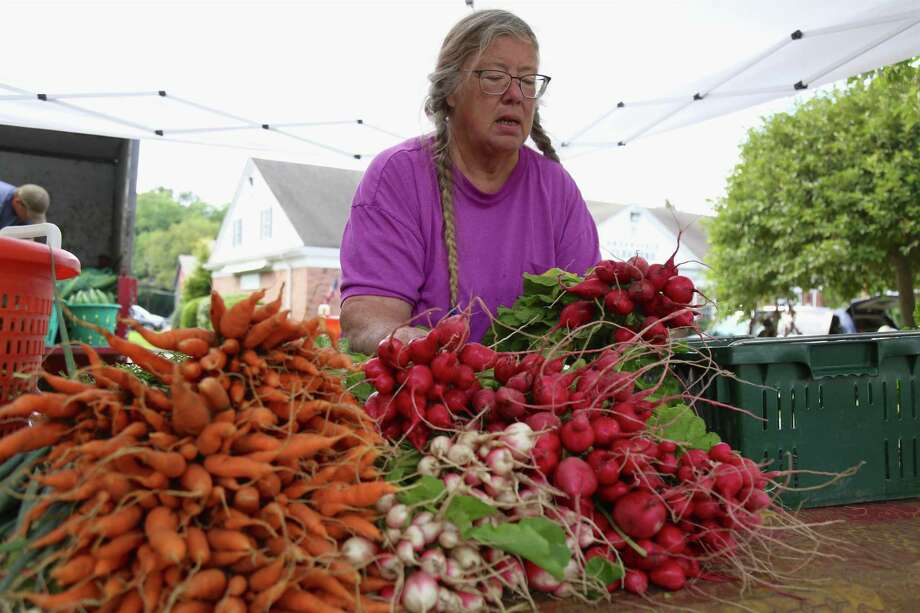 """Punky Wilson of Gazy's Farm in Oxford puts out produce at the Greenfield Hill Farmer's Market on Saturday, Aug. 15, 2020, in Fairfield, Conn. Punky Wilson from Oxford-based Gazy's Farm was one of the many vendors with wares to sell and said the market was very popular. """"The people here are great,"""" Wilson said, noting it's her favorite among many others she does. """"They really support us."""" """"I love to come to this,"""" said Jill Meyer of Westport, who found favor with several ears of fresh corn. """"It's local and it's gonna be fresh."""" Photo: Jarret Liotta / Jarret Liotta / ©Jarret Liotta 2020"""