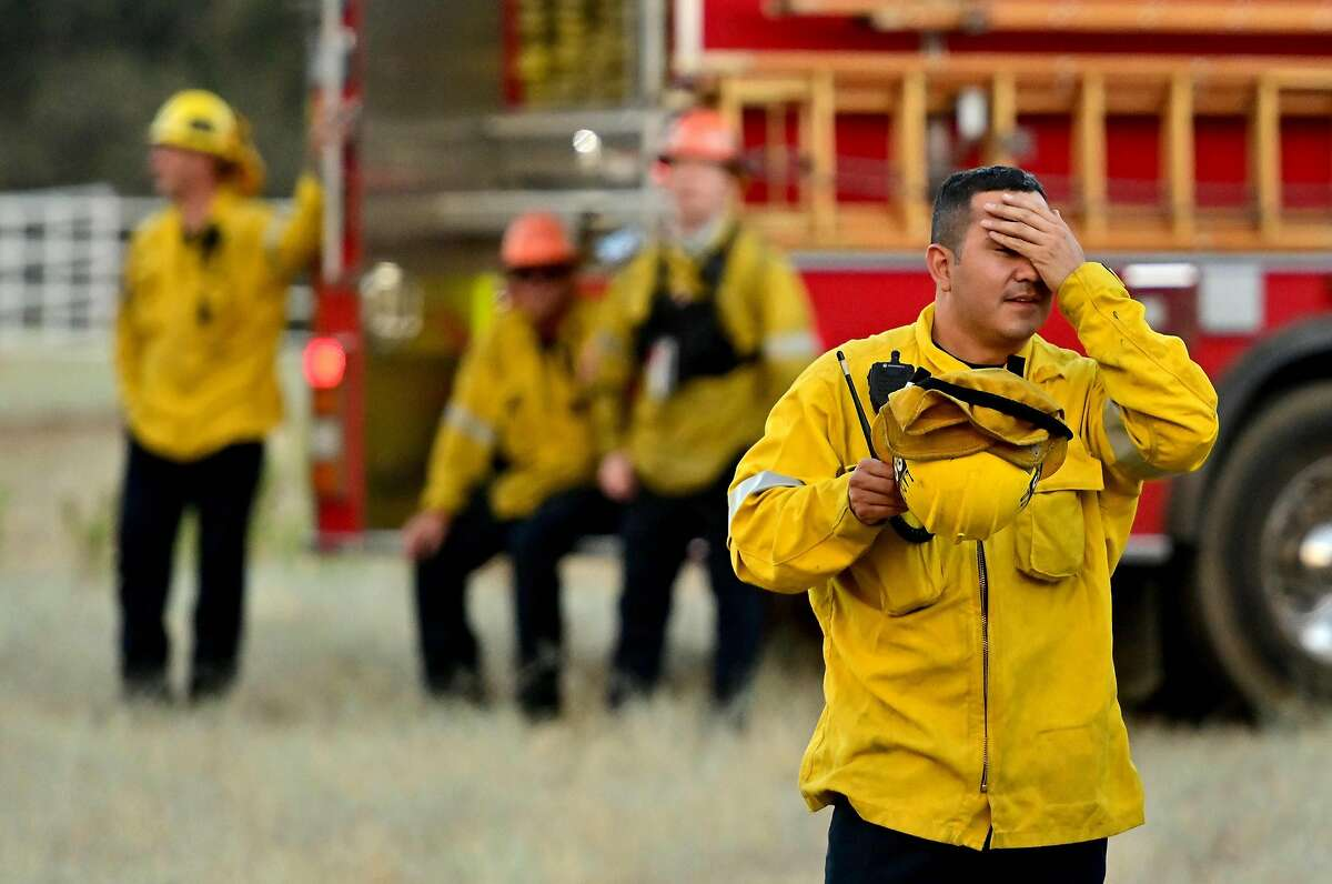Firefighters wait in an open field as flames make their way across a hillside during the Apple fire near Banning, California on August 1, 2020. - 4,125 acres have burn in Cherry Valley, about 2,000 people have received evacuation orders in the afternoon of August 1,2020, and round 8pm PT the fire spread to 12,000 acres. (Photo by JOSH EDELSON / AFP) (Photo by JOSH EDELSON/AFP via Getty Images)