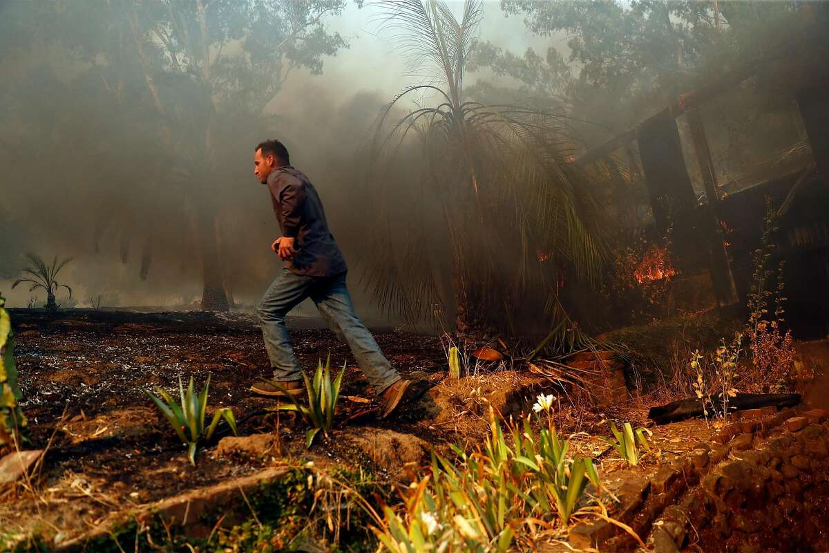 Cantelow resident Sean Deguara runs up a hill while accessing the condition of a neighbor's house that was on fire during LNU Lightning Complex Fire in Vacaville , Calif., on Wednesday, August 19, 2020.