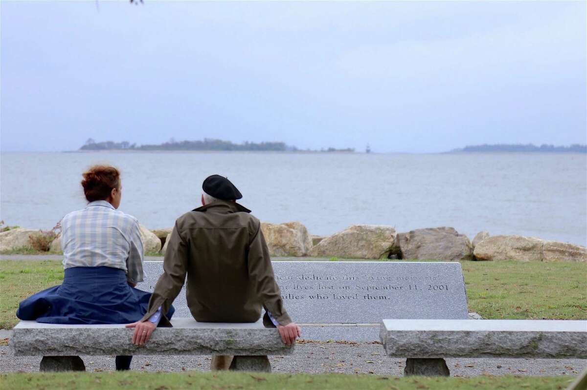 A couple sit by the 9-11 Memorial at Sherwood Island State Park on Sunday, Aug. 16, 2020, in Westport, Conn.