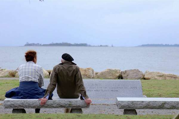 File photo of as two people sit by the 9/11 memorial at Sherwood Island State Park in Westport, Conn., taken on Aug. 16, 2020.