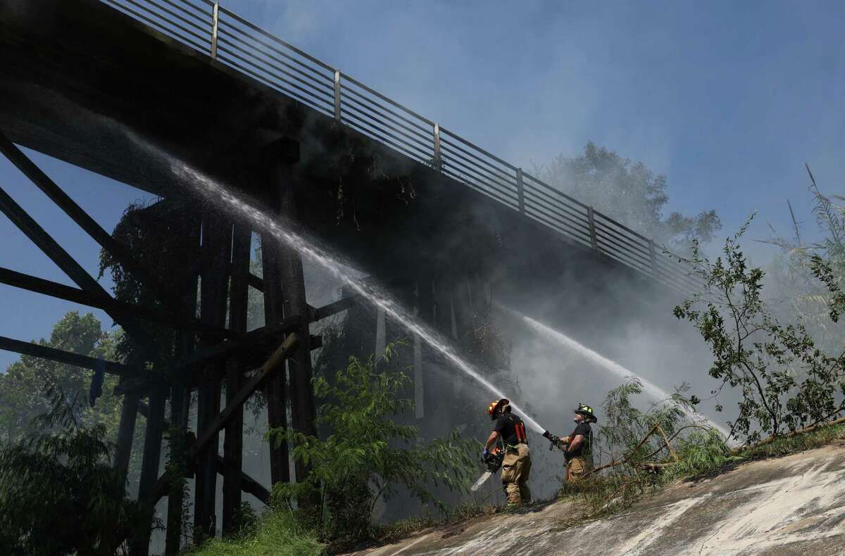 Firefighters work to extinguish a fire on a hike and bike trail bridge Wednesday, August 19, 2020, in the Heights neighborhood in Houston.
