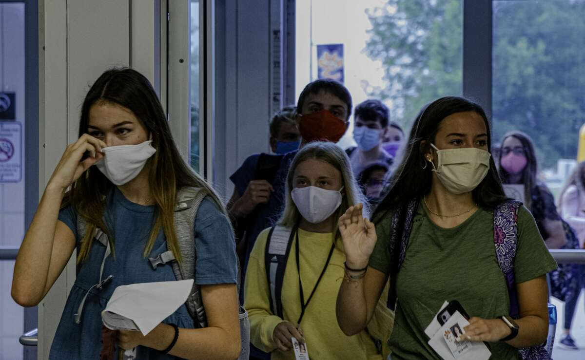 Edwardsville High School students arrive at school wearing face masks on the first day of school Thursday.