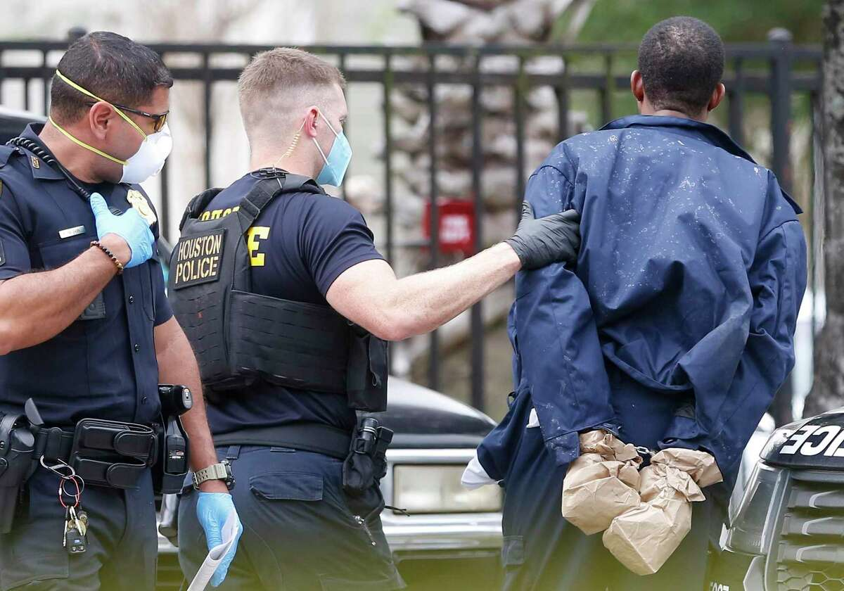 Police take into custody a suspect of a shooting at Concord at Little York apartment complex in Houston on Monday, April 6, 2020.