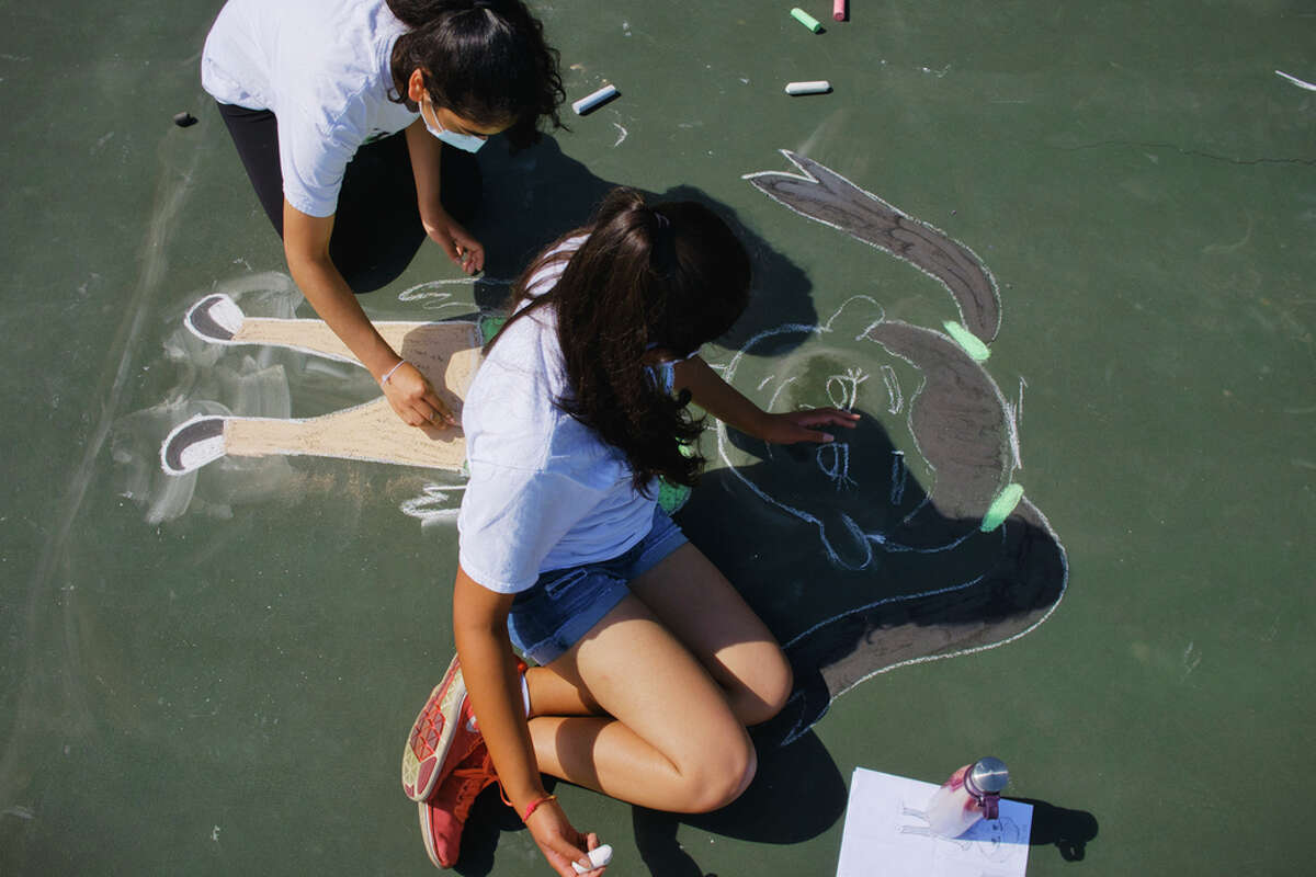 """Sisters, Millee Modasra, 16, left, and Anjalee Modasra, 17, work on their chalk drawing during the 15-LOVE art project called """"10 Blocks"""" at the Westland Hills Tennis Courts on Wednesday, Aug. 19, 2020, in Albany, N.Y. The purpose of the art project is for past and present students to create artwork that focuses on multiculturalism and racial equality. 15-LOVE provides free tennis lessons and educational opportunities to inner-city children in the Capital Region. The 15-LOVE program was able to operate this year but changed where they ran instructions from 9:30am to 8:30pm, with each class being one hour and accommodating four children on the court. (Paul Buckowski/Times Union)"""