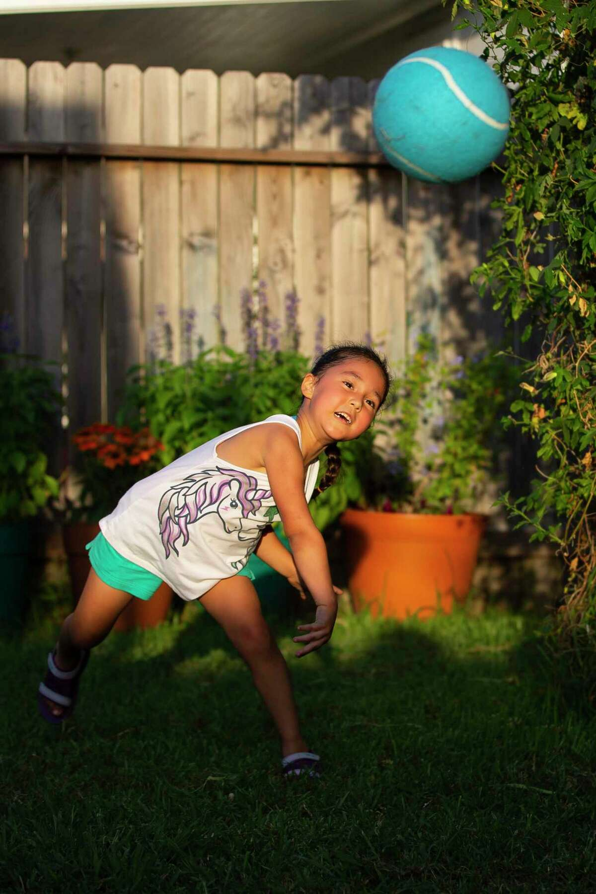 Eliza Burke throws a ball to her mom, Norma, while playing in the backyard.