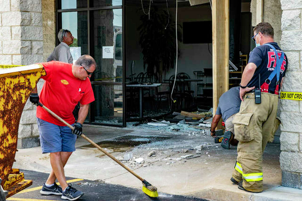 Cleanup crews work to clear debris and board up the front of the Orient Wok Chop Suey Wednesday afternoon.
