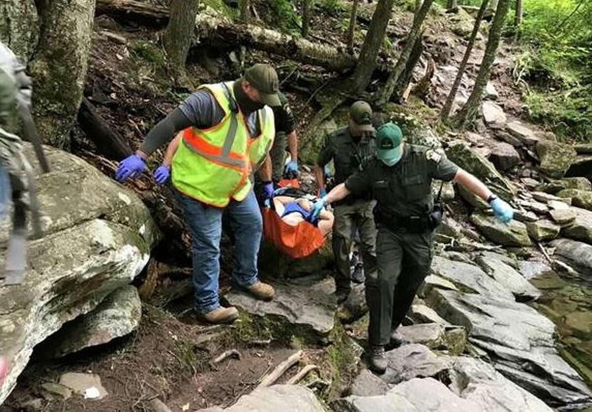 Forest Rangers and EMS personnel carry injured 74-year-old woman from the Blue Hole access trail.